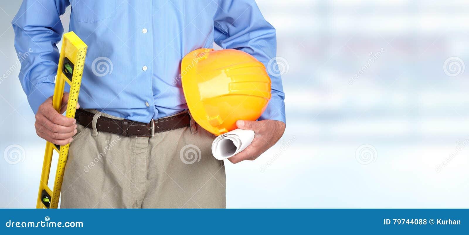 Manos del trabajador de construcción con el casco y el nivel