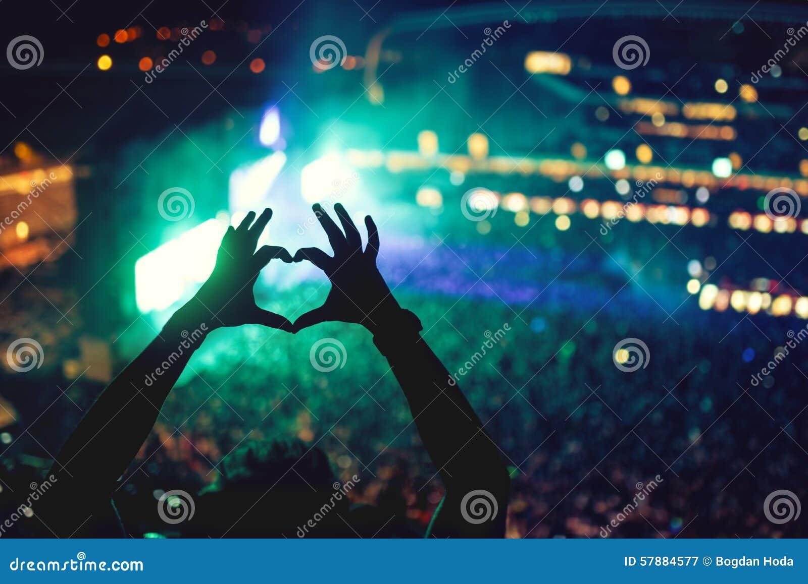 Manos en forma de corazón en el concierto, amando el artista y el festival Concierto de la música con las luces y la silueta de u