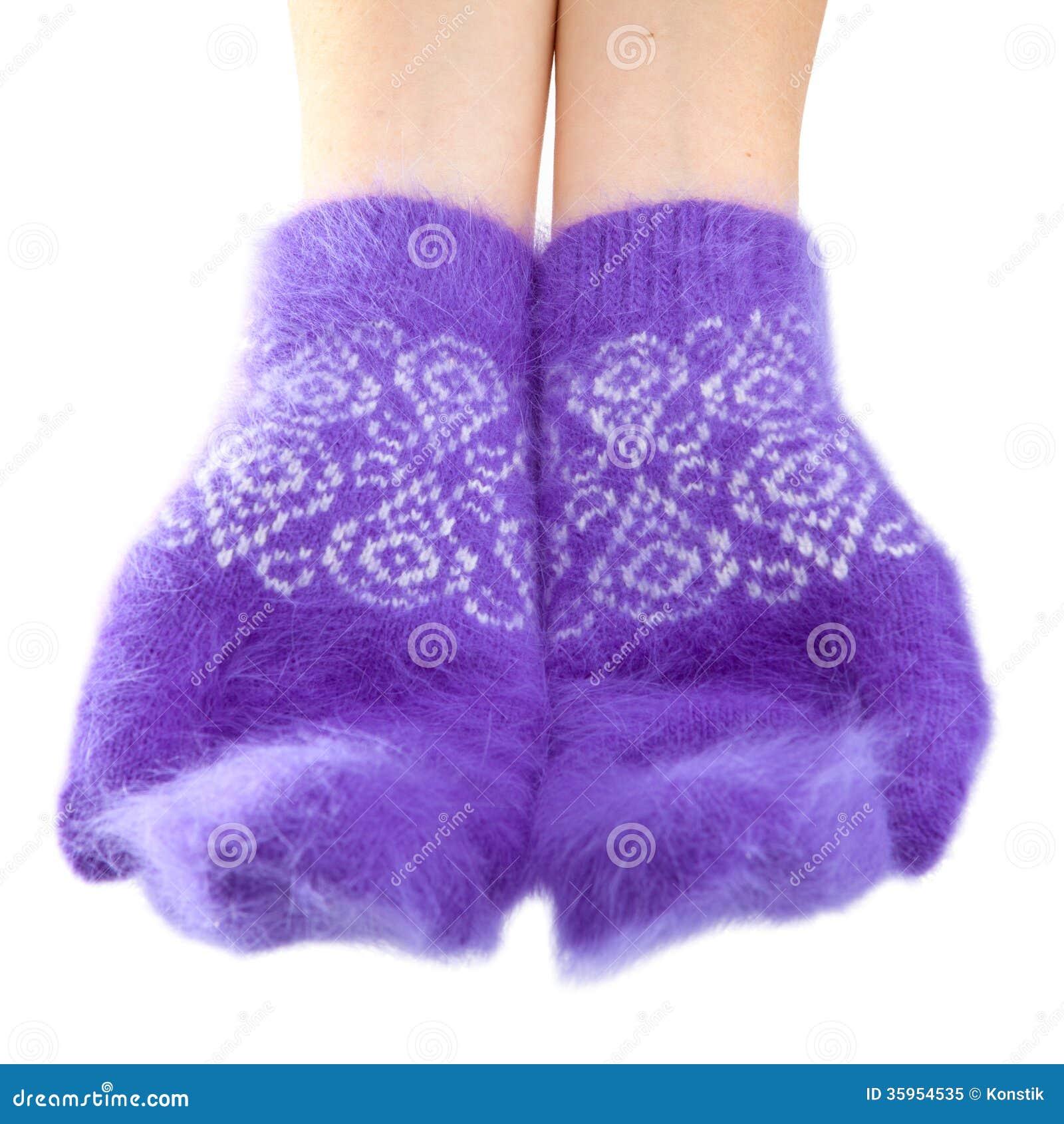 Manos en manoplas mullidas de la lila en un fondo blanco