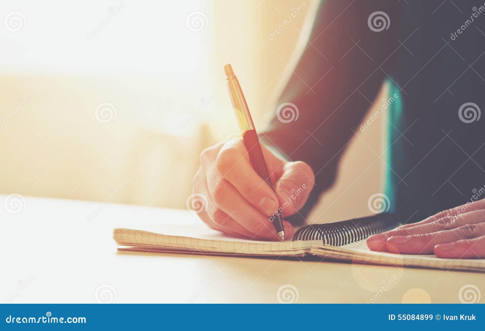 Manos femeninas con la escritura de la pluma
