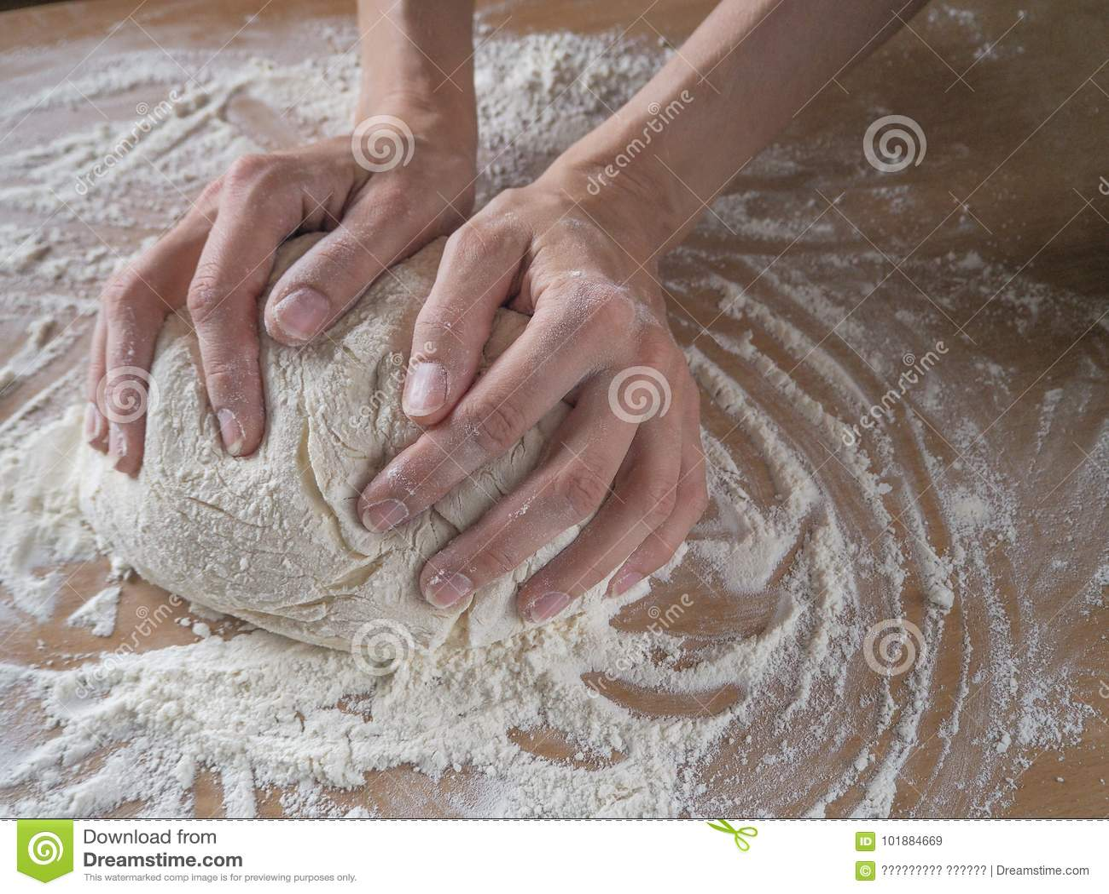 Manos femeninas que hacen la pasta para la pizza