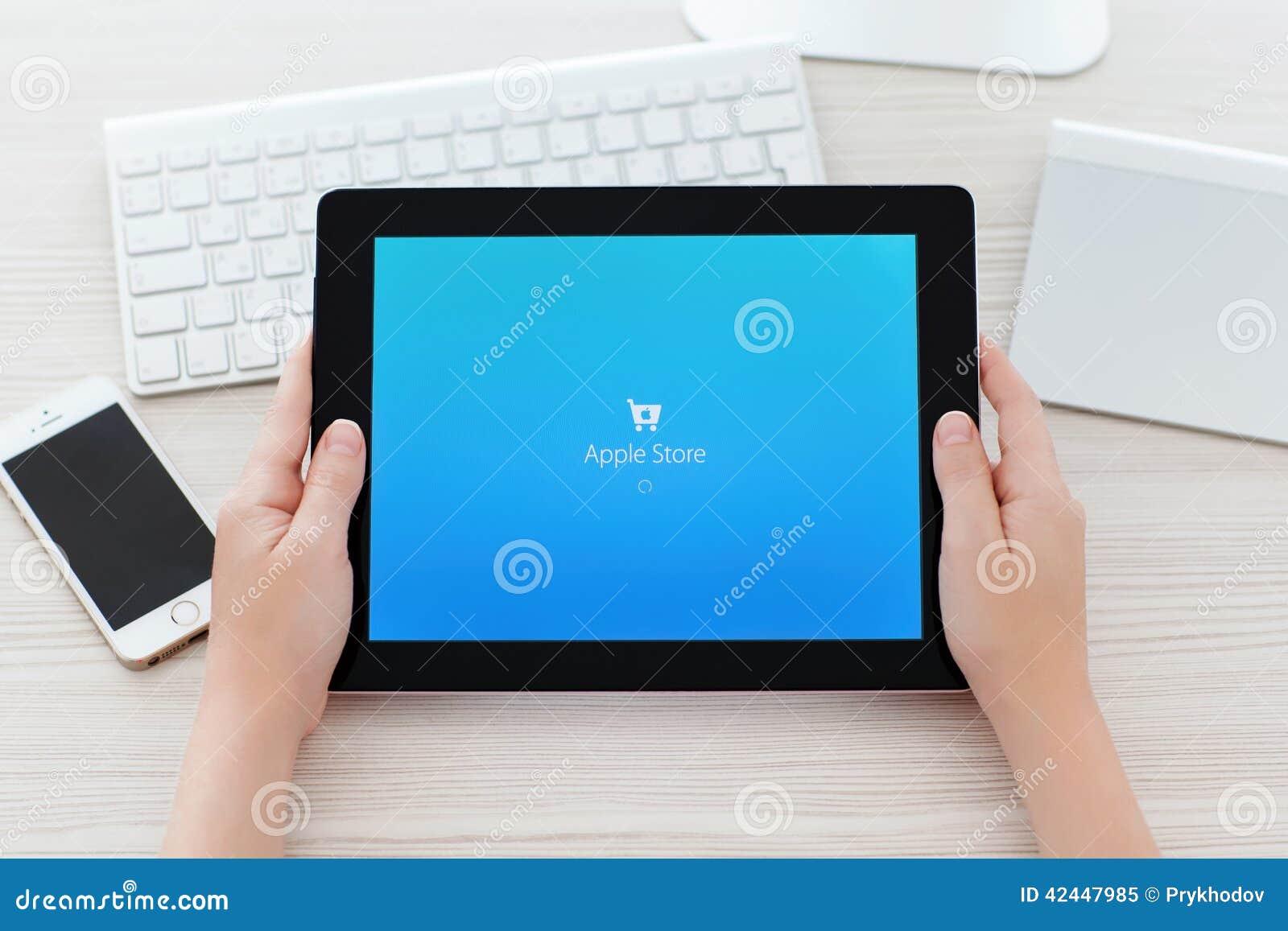 Manos femeninas que llevan a cabo el iPad con app Apple Store en el abo de la pantalla