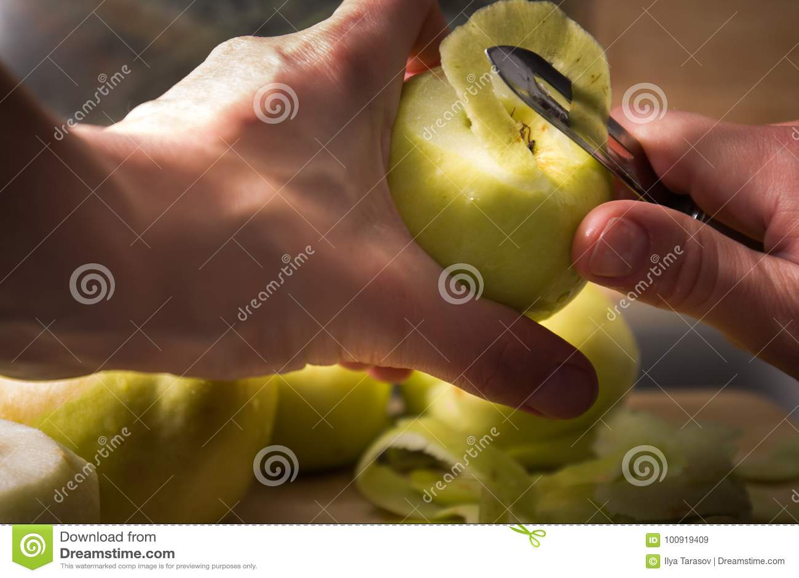 Manos femeninas que pelan la piel apagado de la manzana verde usando un cuchillo de pelado