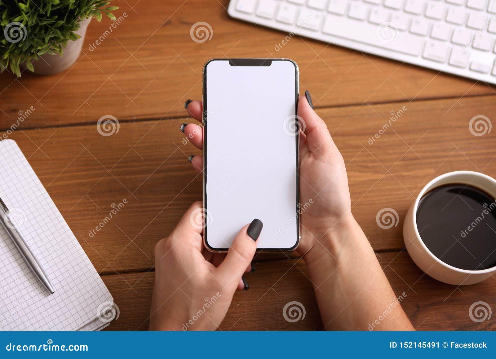 Manos femeninas que sostienen el teléfono elegante con la pantalla vacía en blanco blanca en la tabla marrón del escritorio
