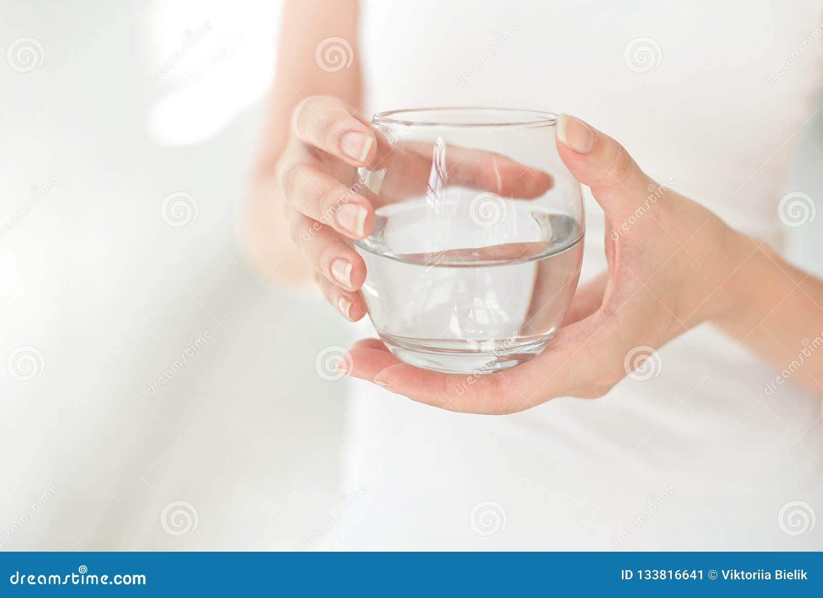 Manos femeninas que sostienen un vidrio claro de agua Un vidrio de agua mineral limpia en manos, bebida sana
