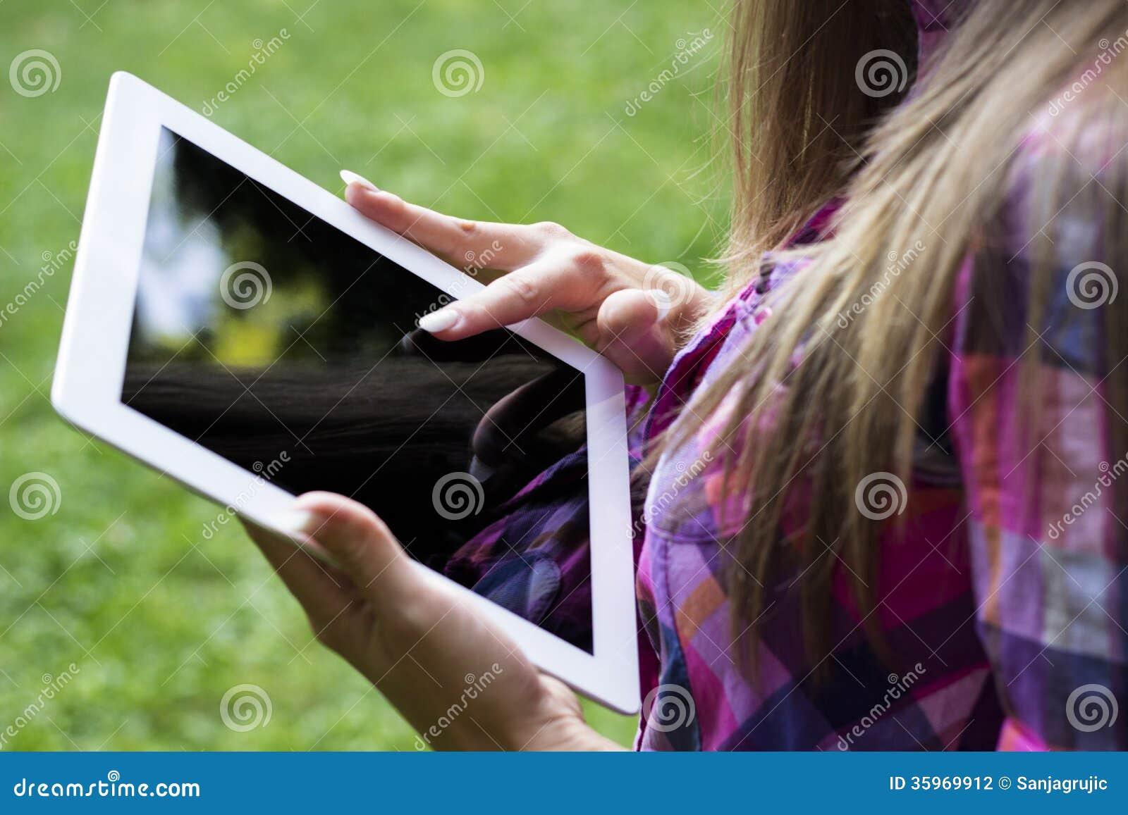 Manos femeninas usando una tableta digital
