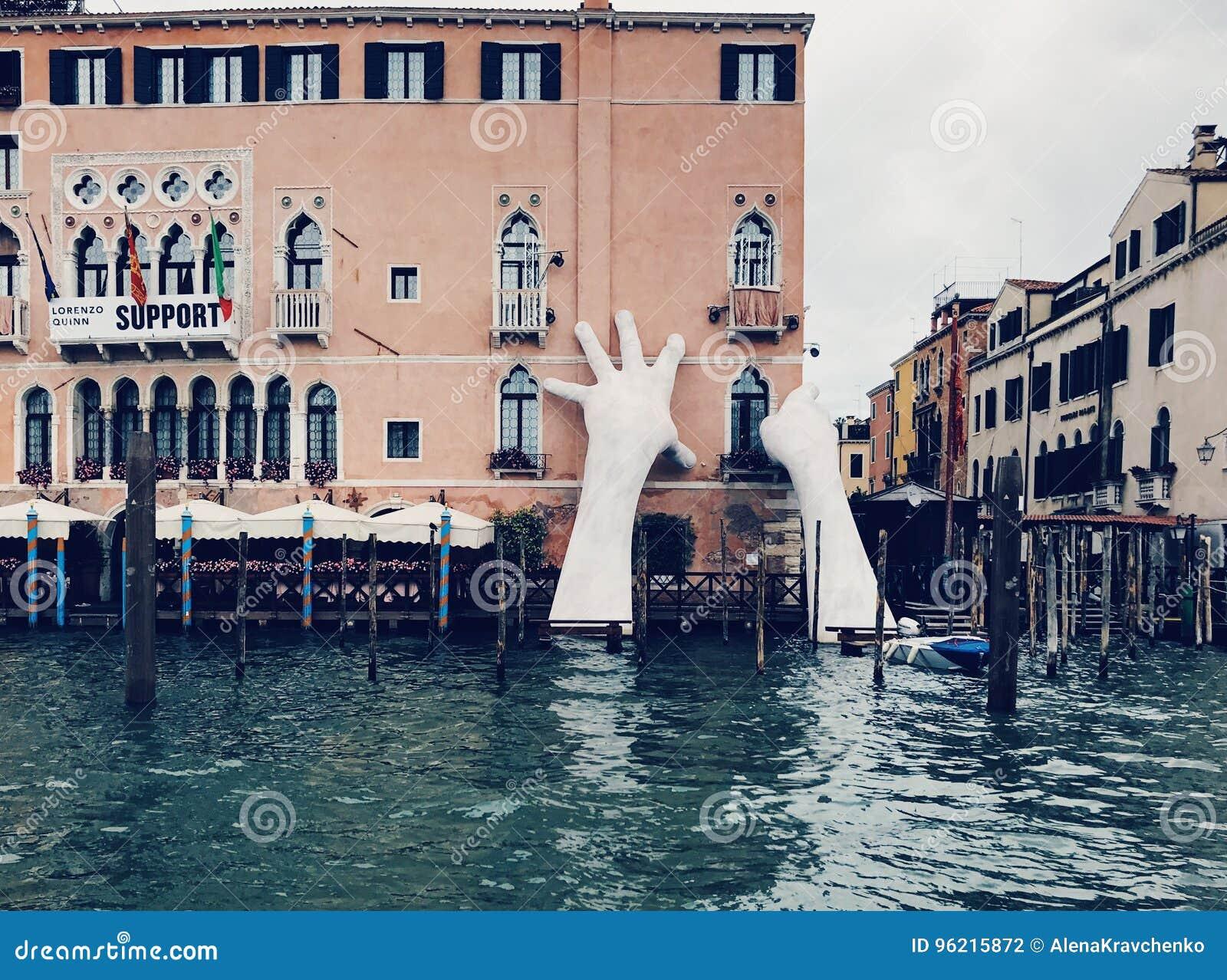 Manos gigantescas que suben del agua para apoyar el hotel de Ca' Sagredo, Venecia
