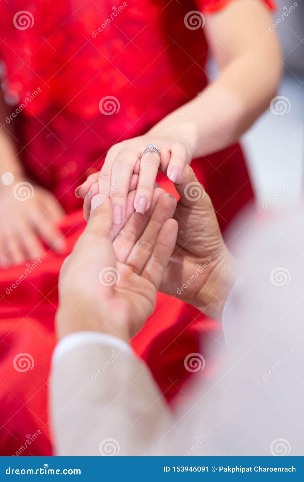 Manos hermosas de novia y del novio que intercambian los anillos de bodas en iglesia durante ceremonia de boda matrimonio santo e