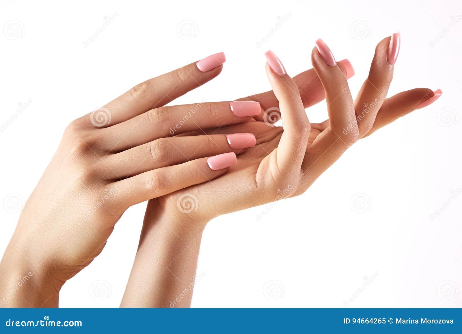 Manos hermosas del ` s de la mujer en fondo ligero Cuidado sobre la mano Palma blanda Manicura natural, piel limpia Clavos rosado