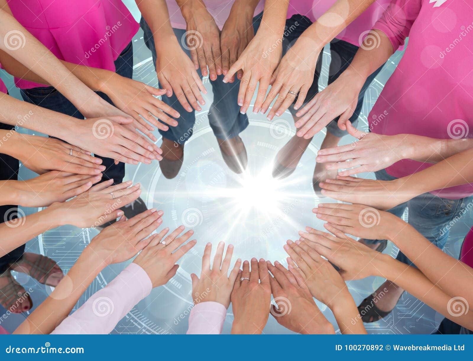 Manos junto en círculo sobre luz porta brillante con las camisetas rosadas