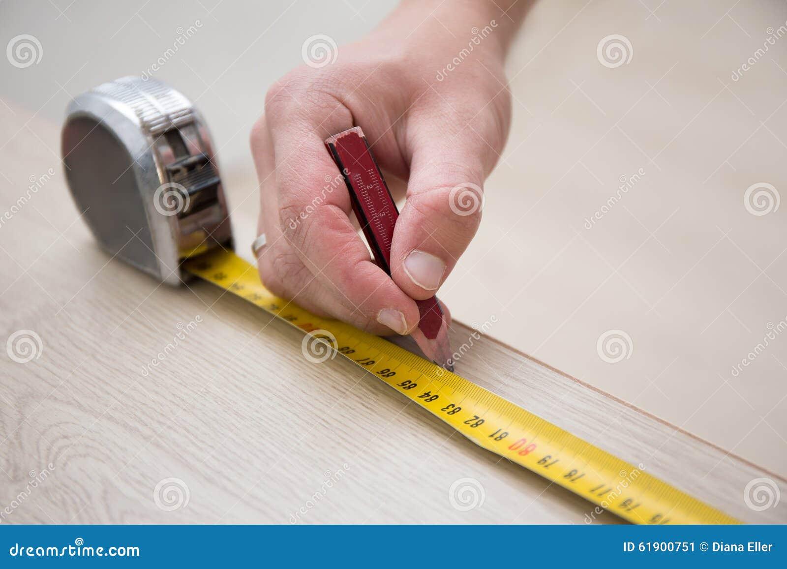 Manos masculinas con la cinta métrica y el nuevo piso de madera laminado
