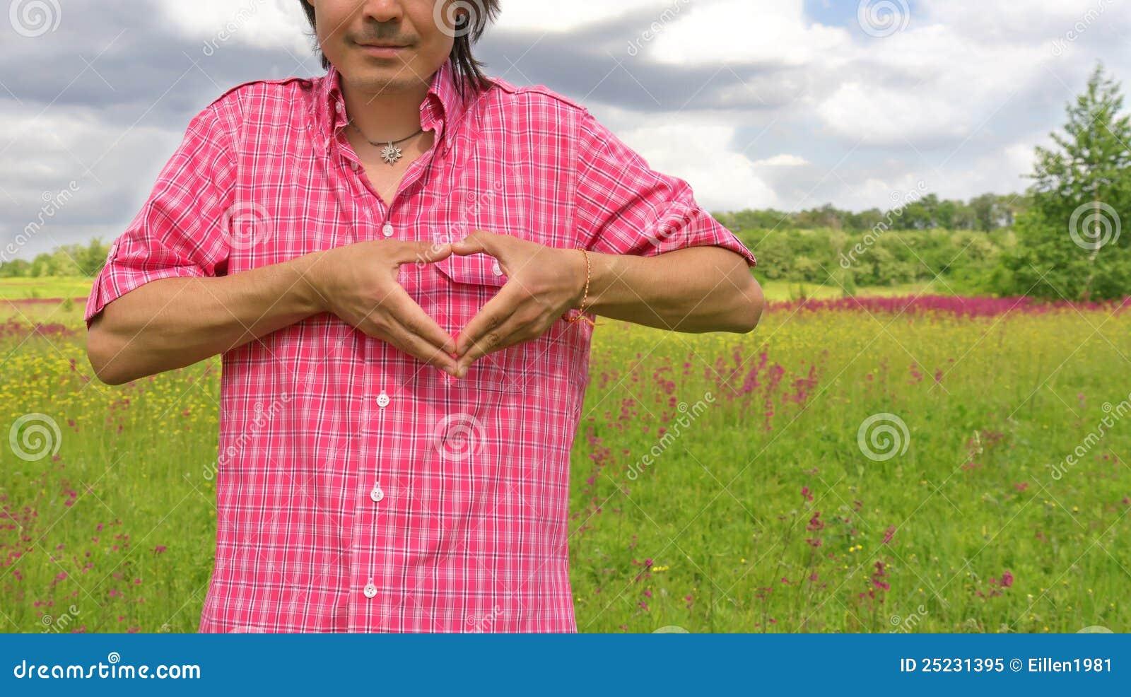 Manos masculinas en la dimensión de una variable del corazón en una naturaleza