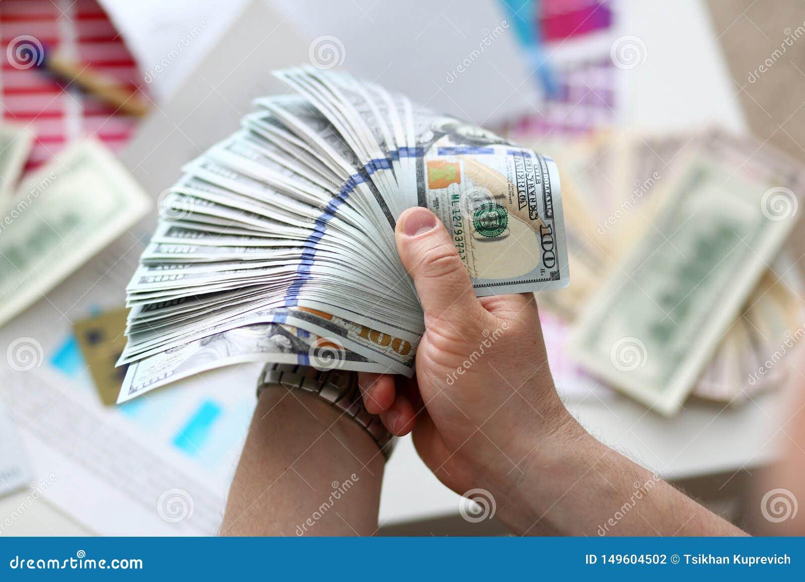 Manos masculinas que cuentan el dinero del paquete enorme