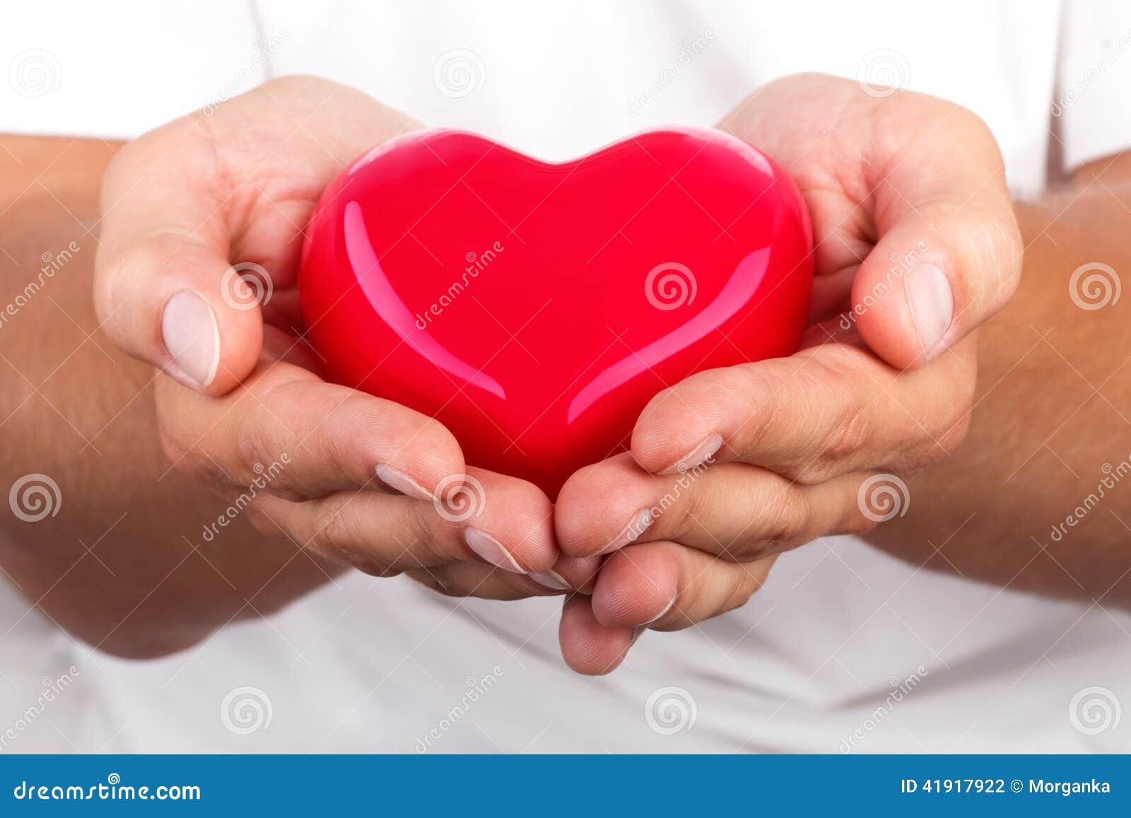 Manos masculinas que dan el corazón rojo