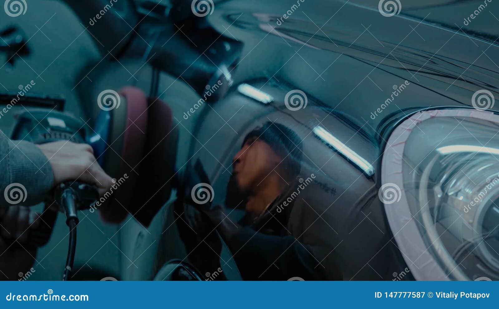 Manos polacas del trabajador de la cera del coche que aplican la cinta protectora antes de pulir Coche que pulimenta y de pulido