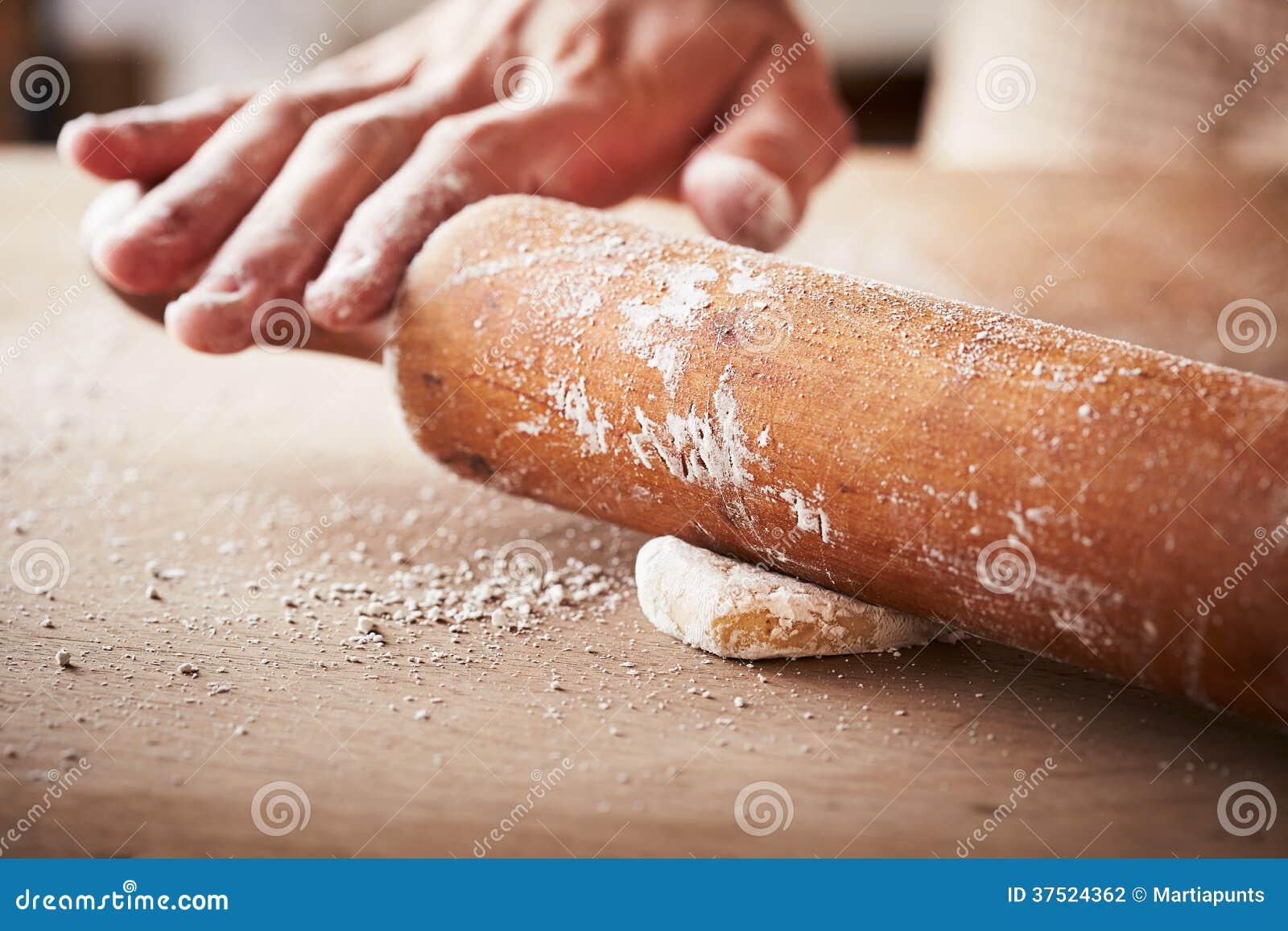 Manos que cuecen la pasta con el rodillo