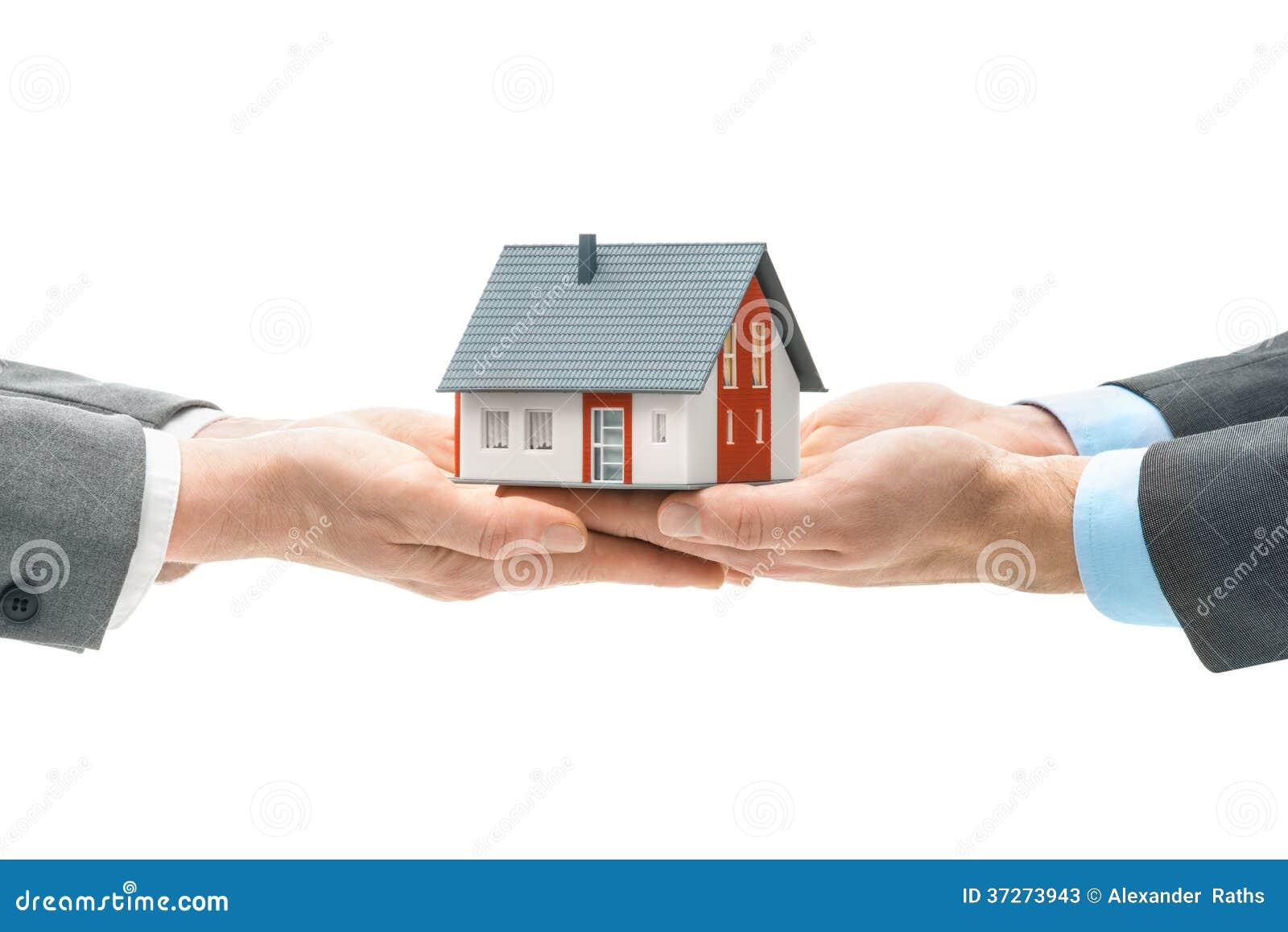 Manos que dan el modelo de la casa a otras manos