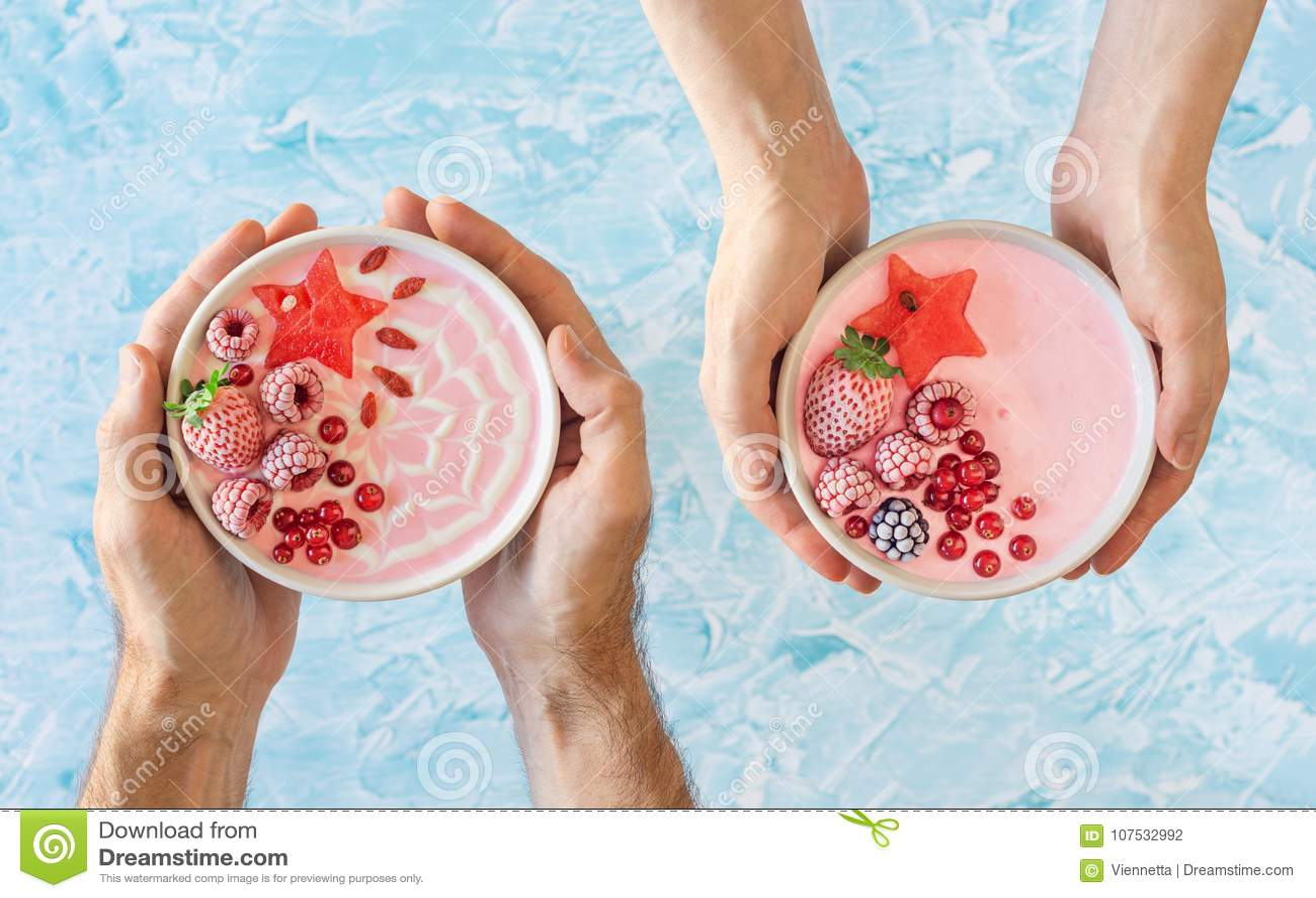 Manos que detienen a Berry Yogurt Smoothie Bowls rosado