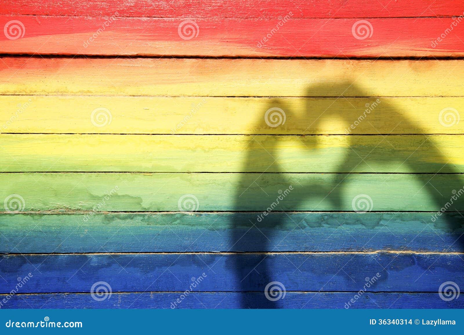 Manos que hacen la sombra del corazón del amor en fondo del arco iris