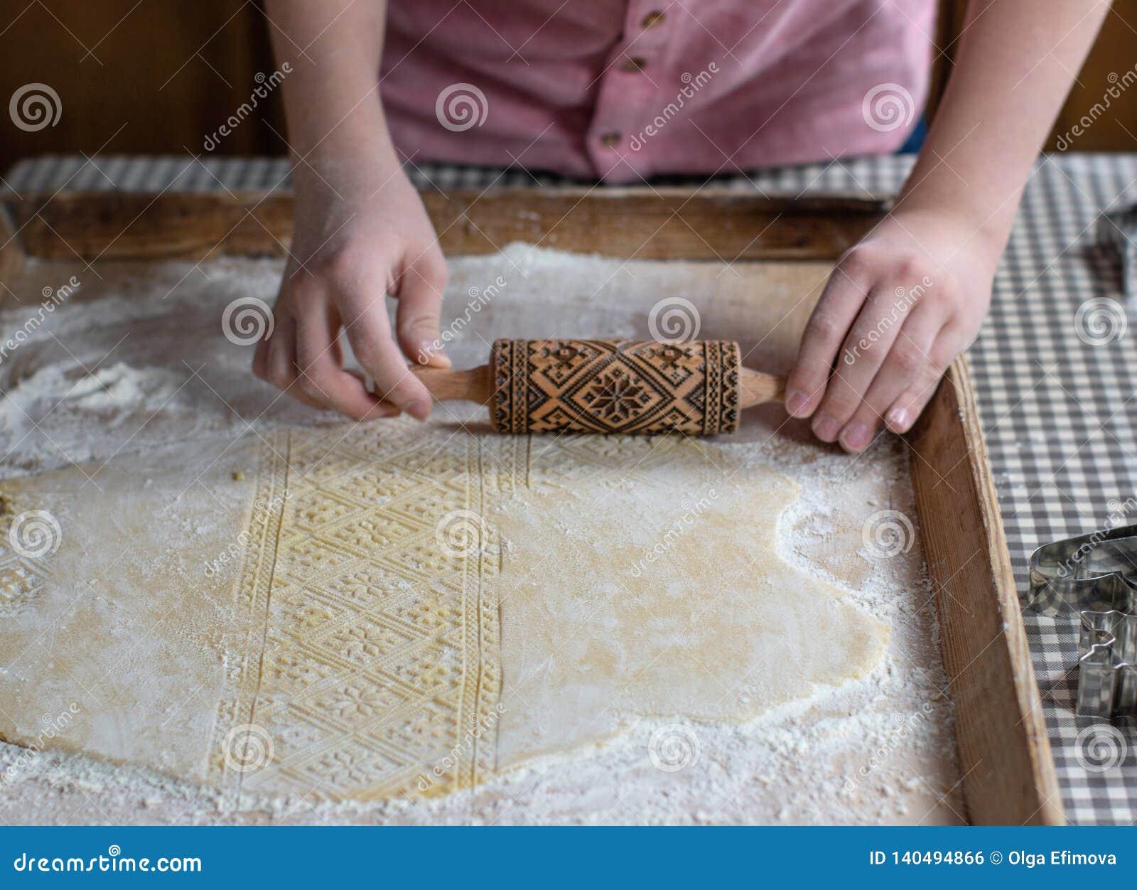 Manos que ruedan la pasta con un rodillo de grabación en relieve, en un fondo de madera