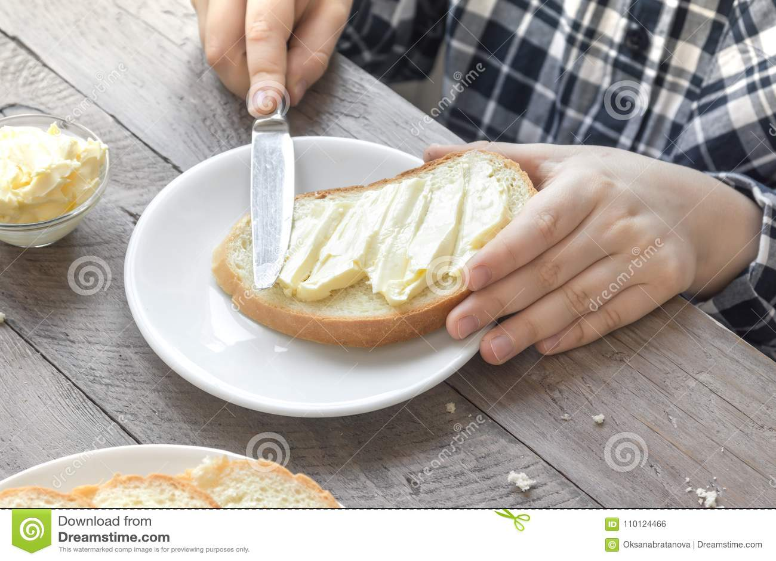 Manos que separan la mantequilla en el pan