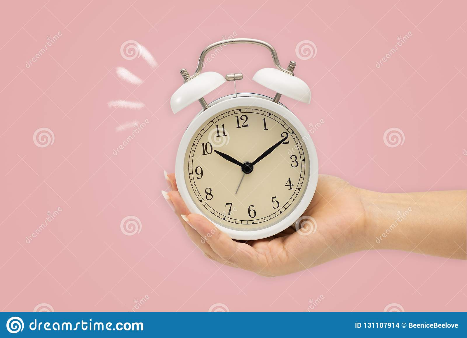 Manos que sostienen el despertador en bacground rosado