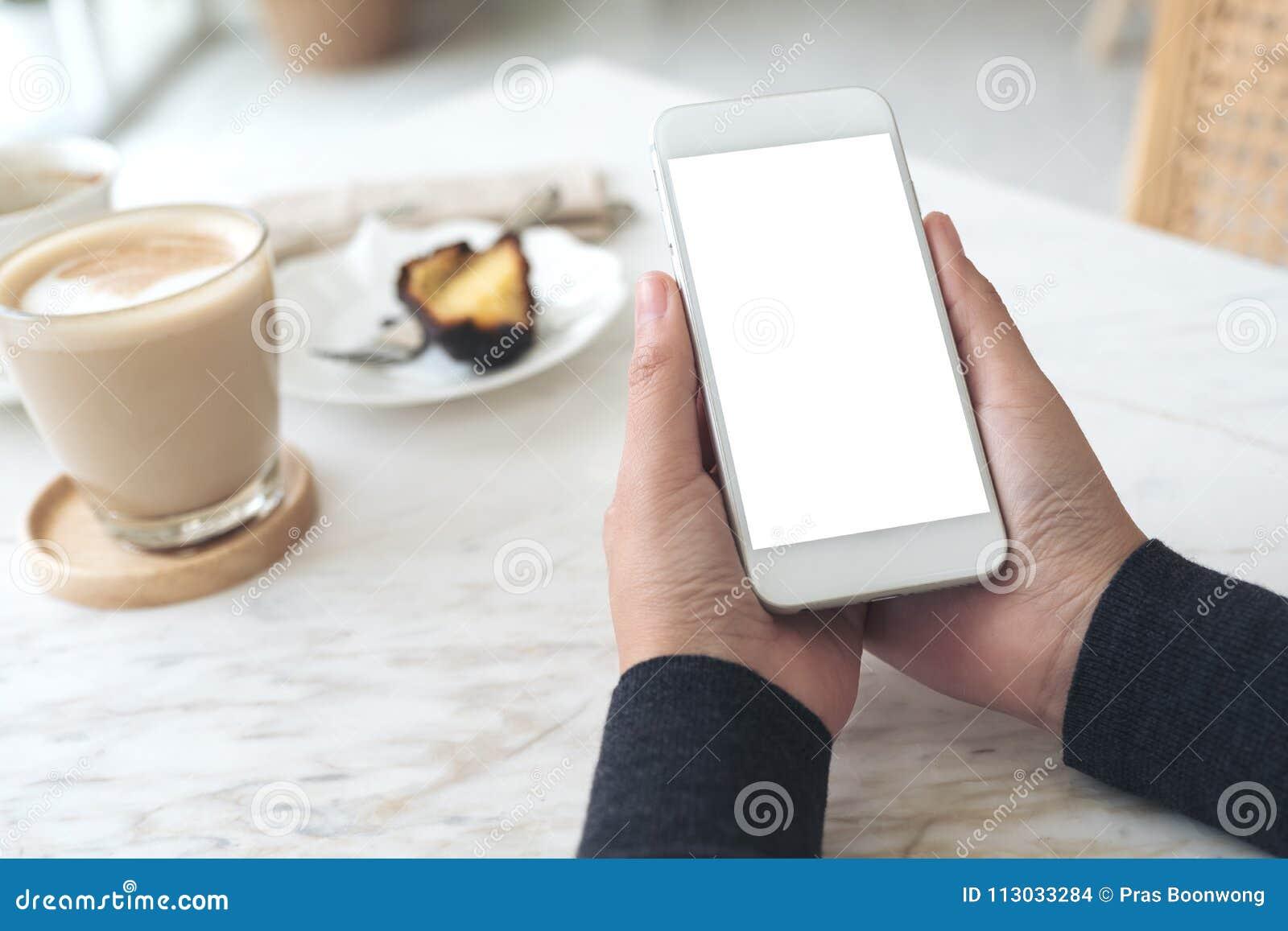 Manos que sostienen el teléfono móvil blanco con la pantalla en blanco con una taza de café y de bocado en la tabla en café