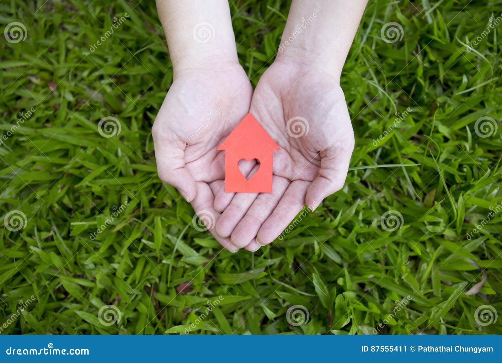 Manos que sostienen la casa de papel roja
