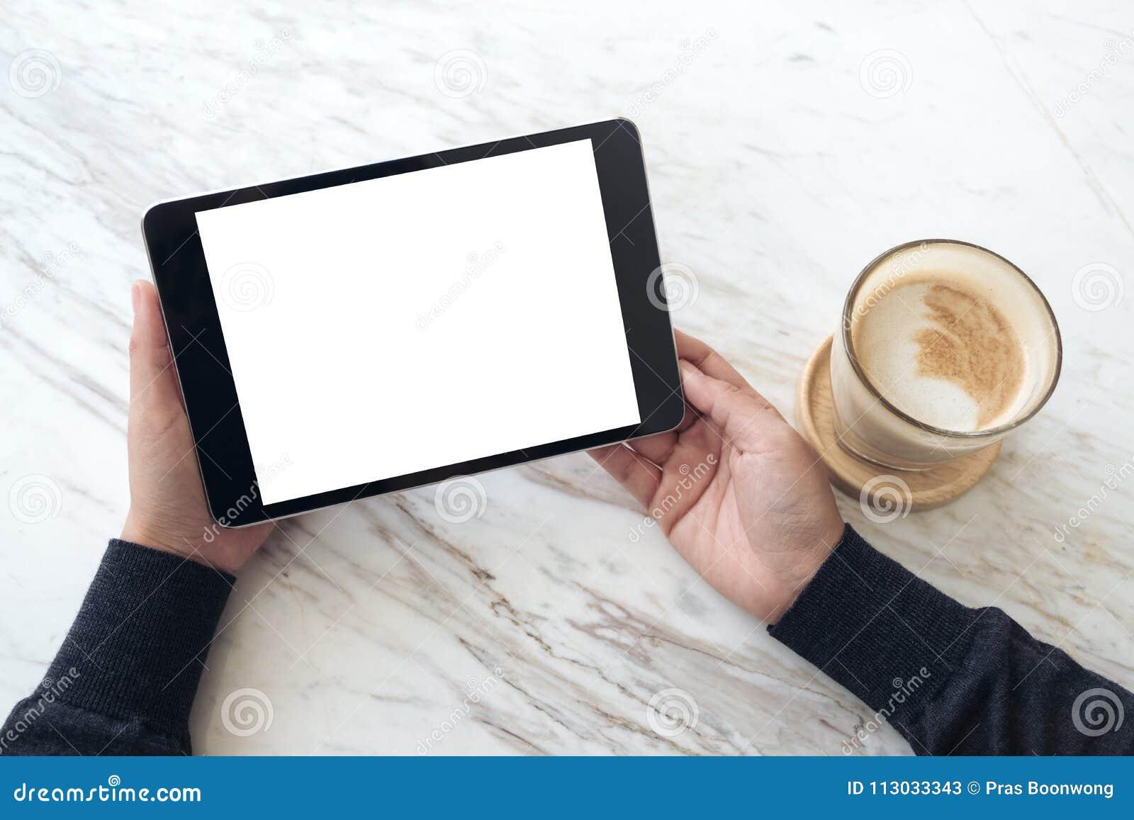 Manos que sostienen la PC negra de la tableta con la pantalla en blanco y la taza de café blancas en fondo de la tabla