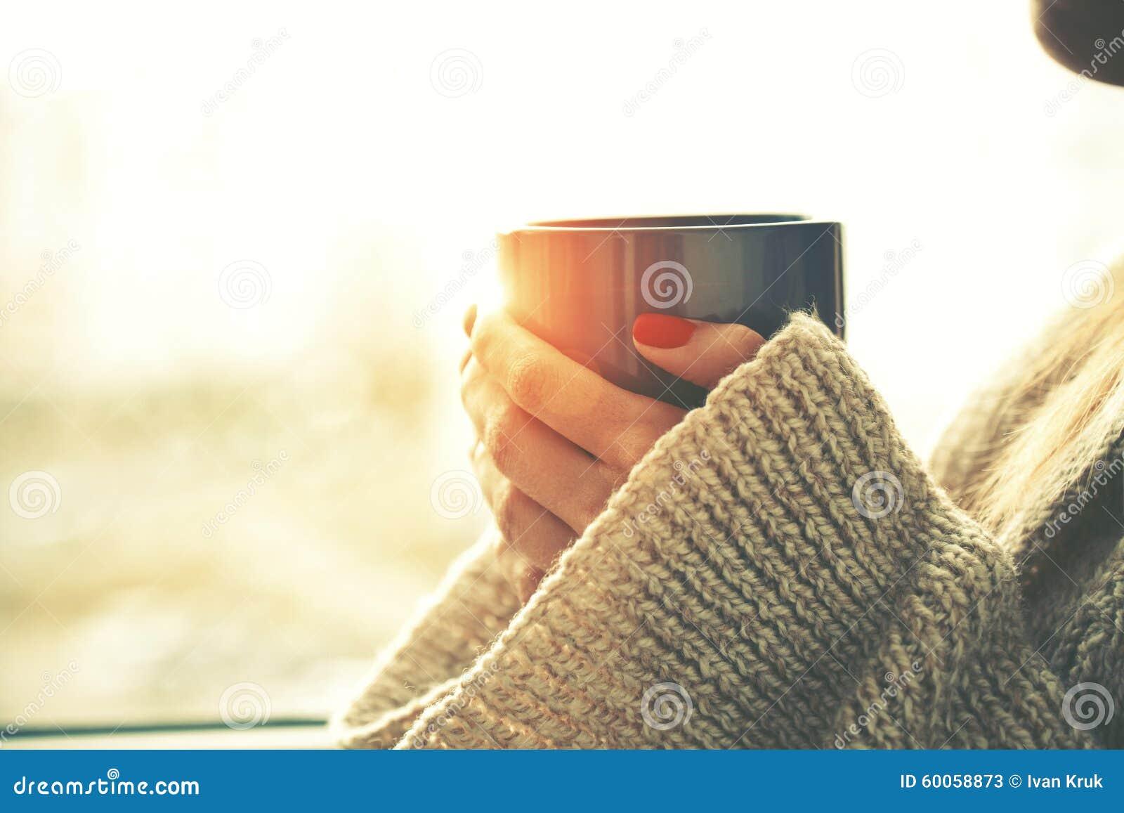 Manos que sostienen la taza caliente de café o de té