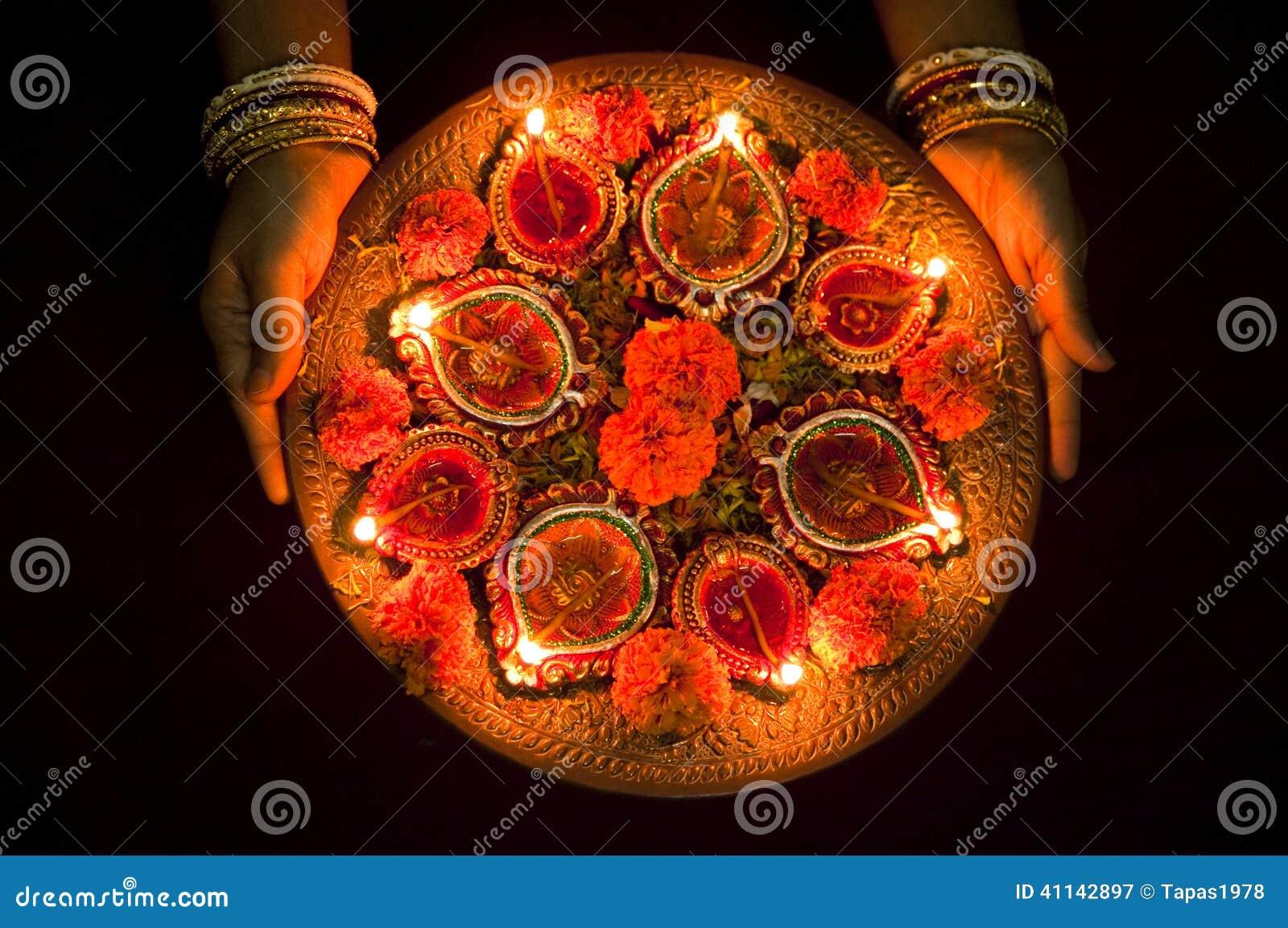 Manos que sostienen las lámparas de Diwali