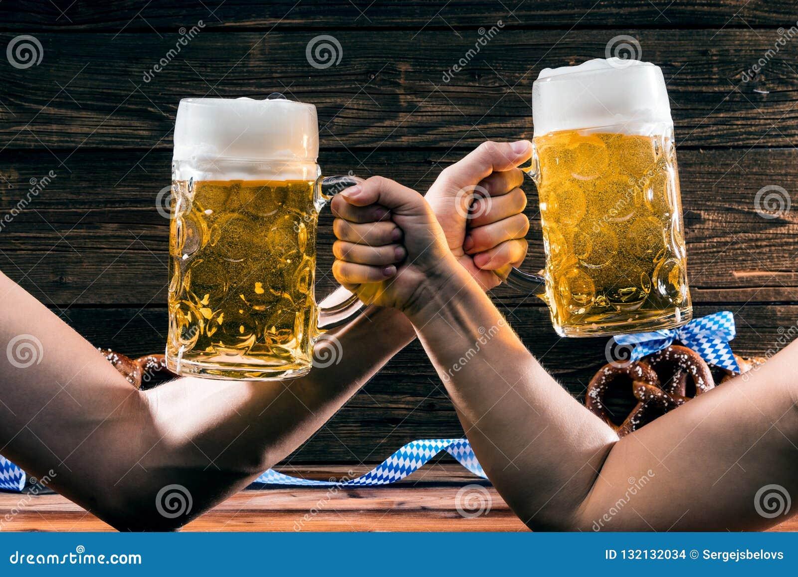 Manos que sostienen las tazas de cerveza bávara Oktoberfest