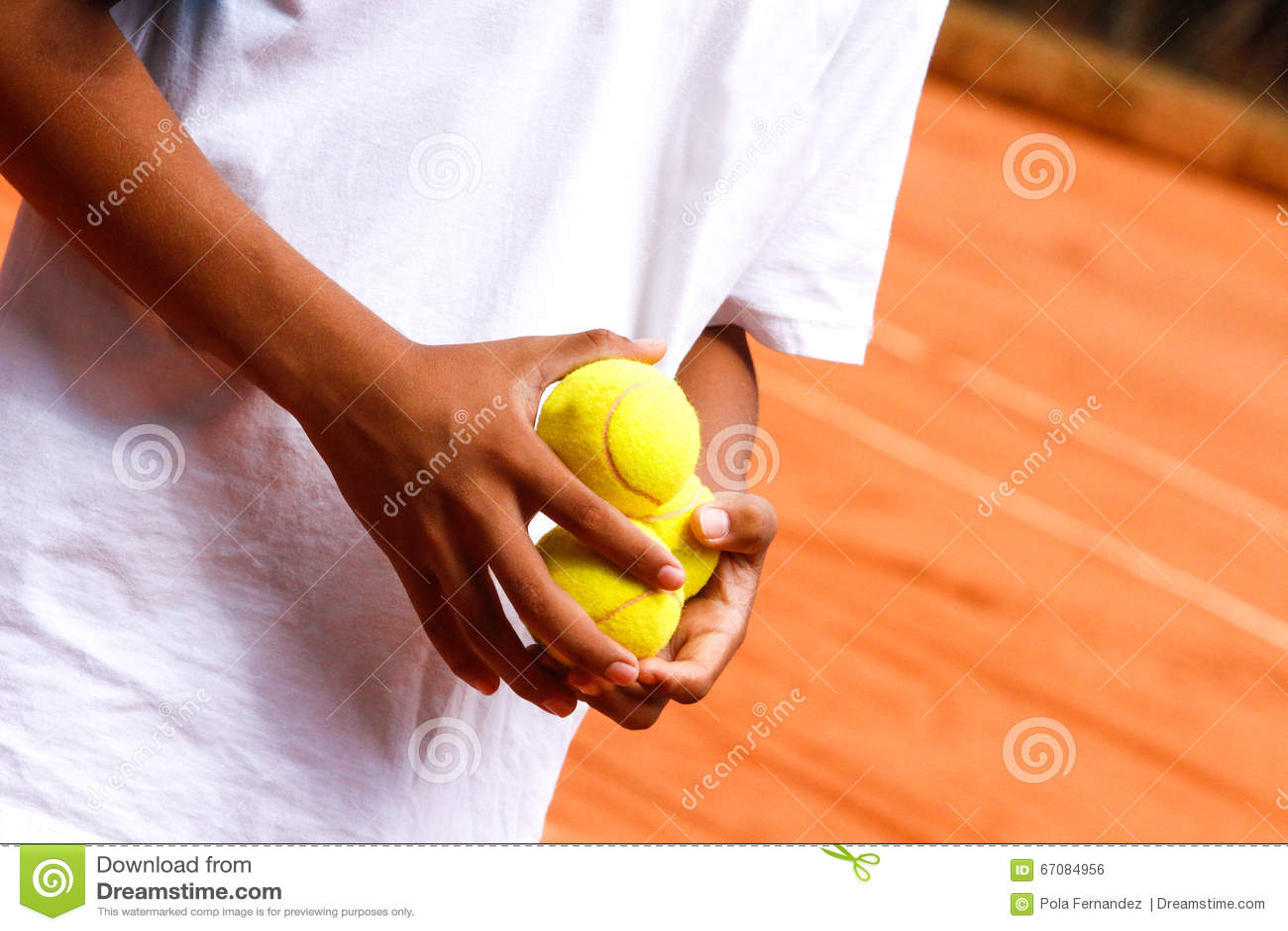 Manos que sostienen pelotas de tenis