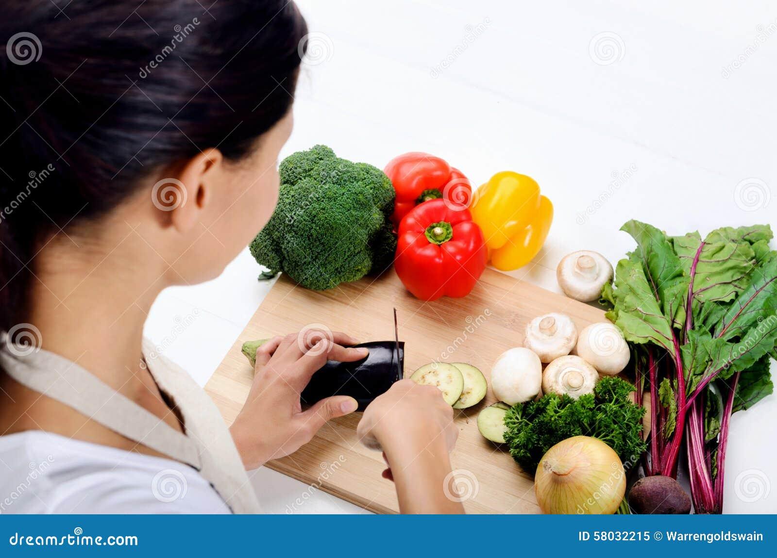 Manos que sostienen verduras del corte del cuchillo