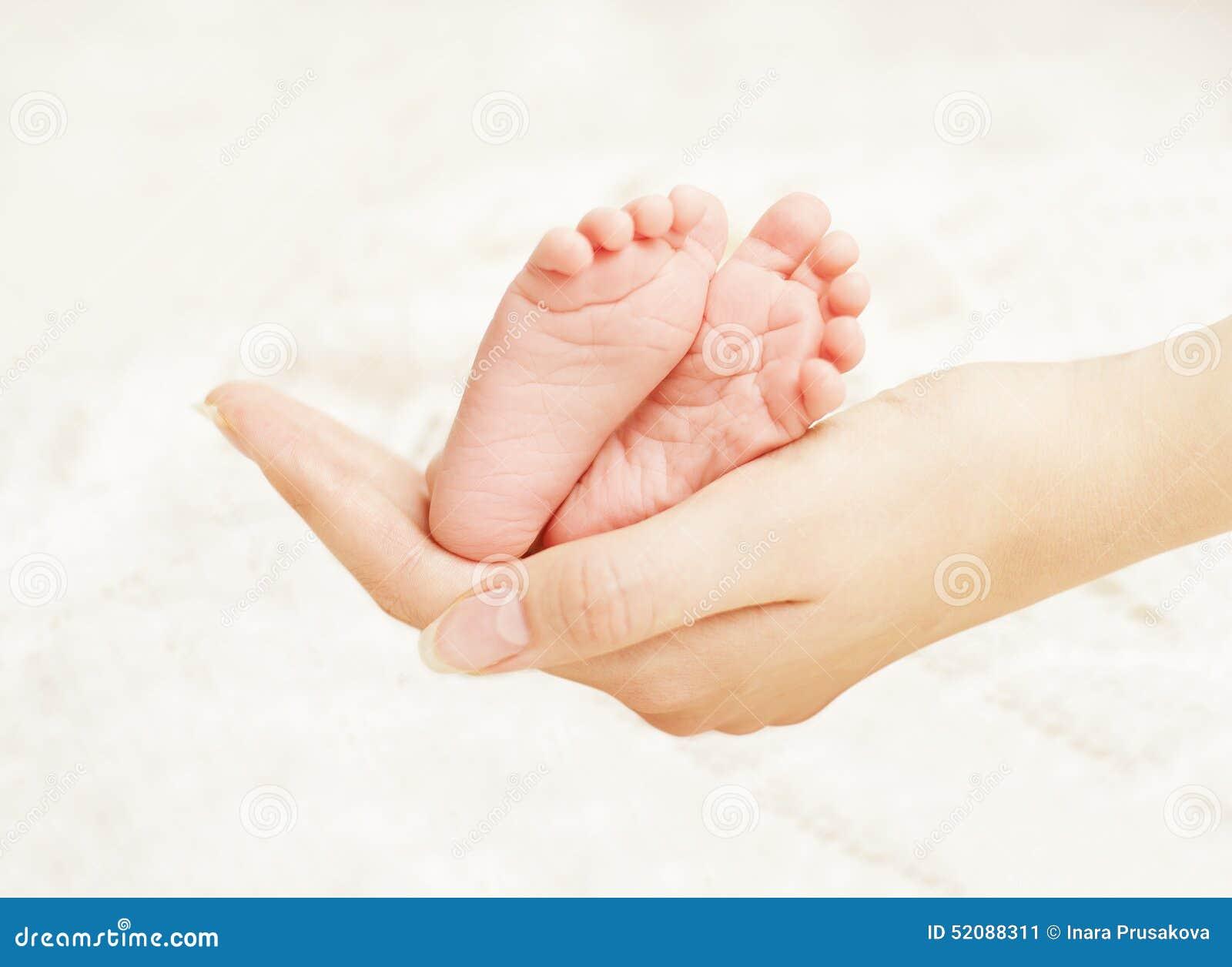 Manos recién nacidas de la madre de los pies del bebé Pie recién nacido del niño, amor de la familia