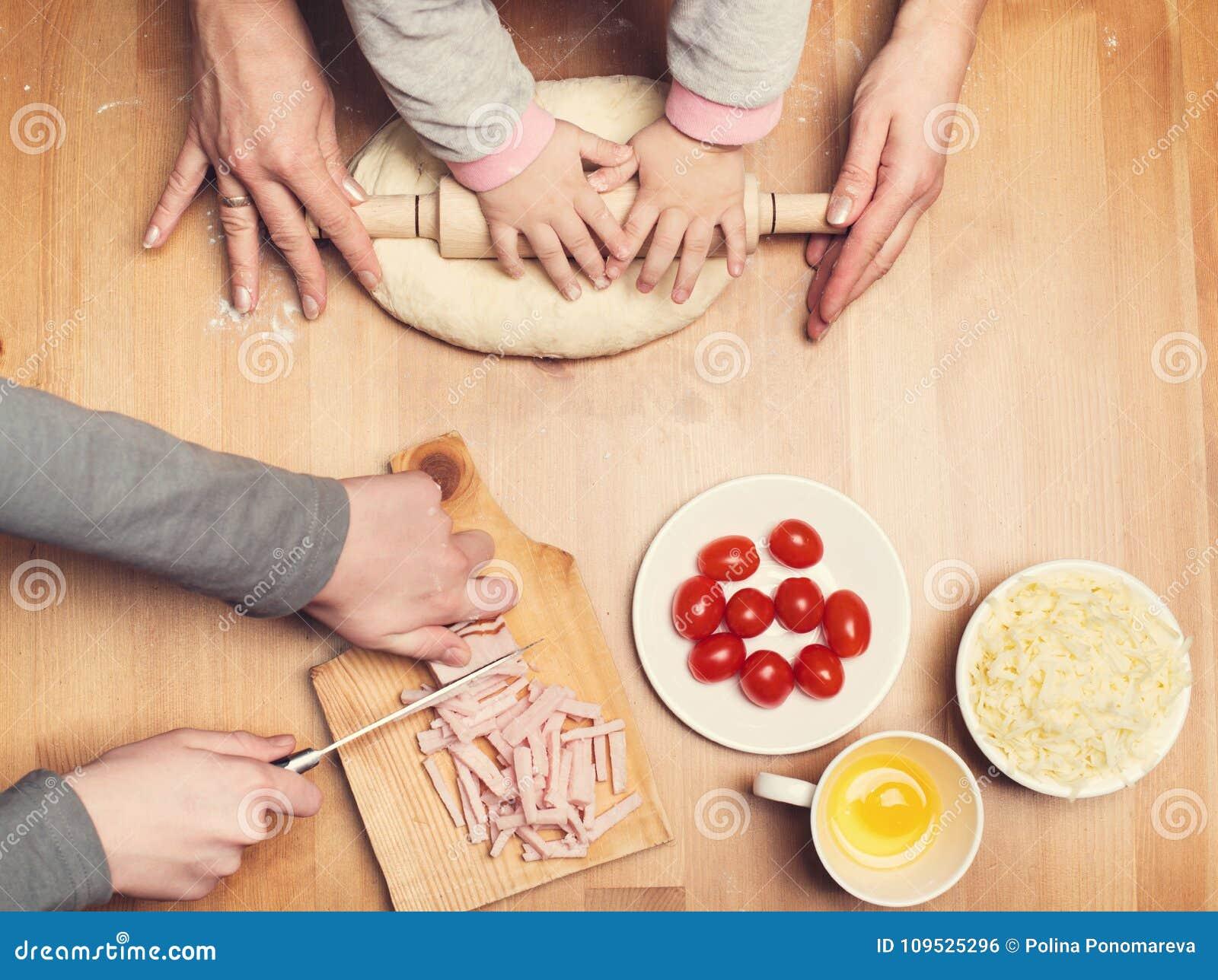 Manos trabajadoras El cocinar con los niños Mano del niño y de la madre