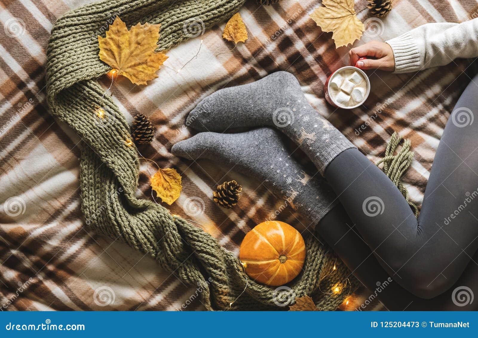 Manos y pies del ` s de las mujeres en el suéter y los calcetines grises acogedores de lana que sostienen la taza de café calient