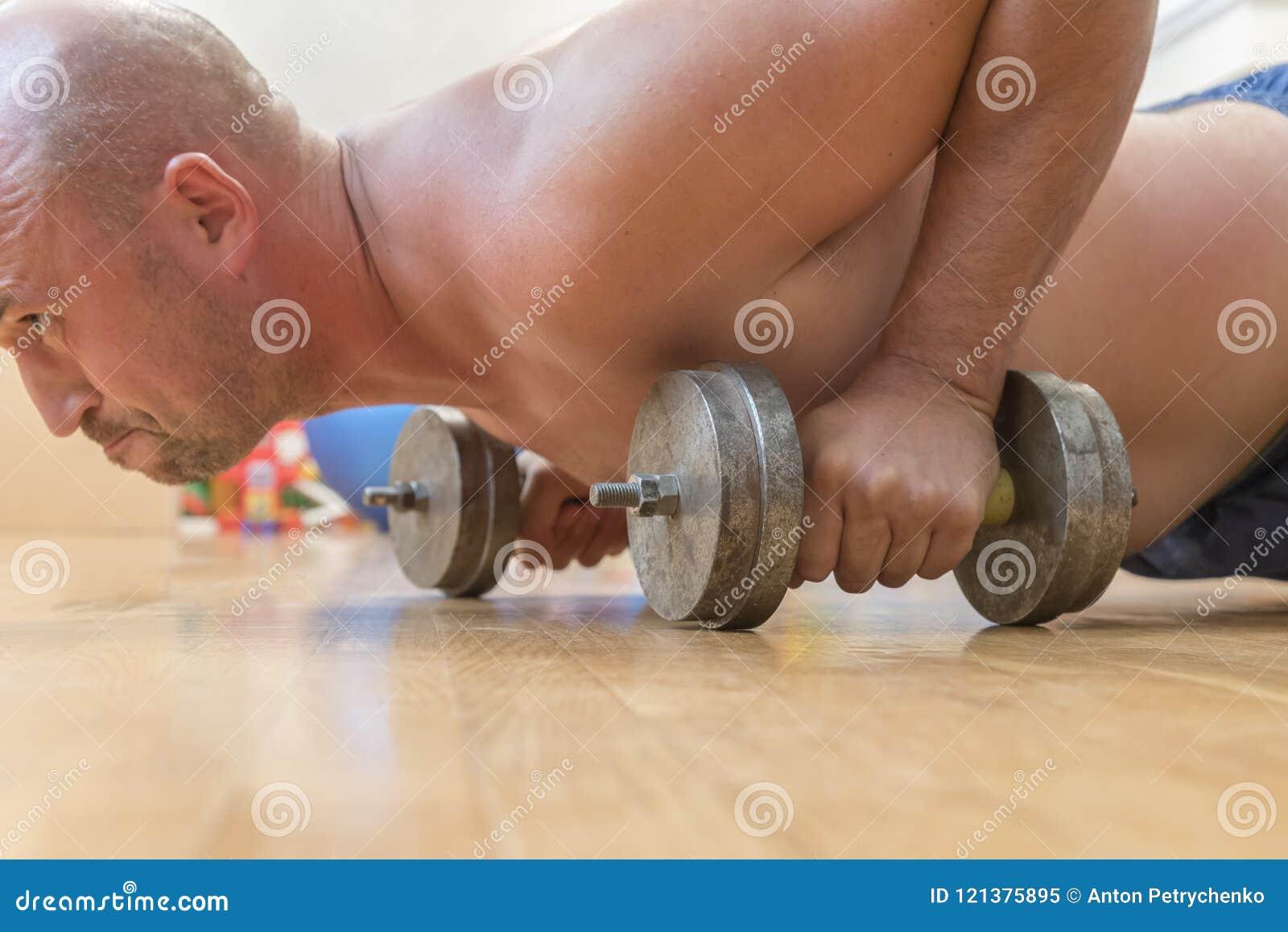 Manpressarna från golvet close upp Begreppet av en sund livsstil och sport Den skalliga mannen går in för sportar