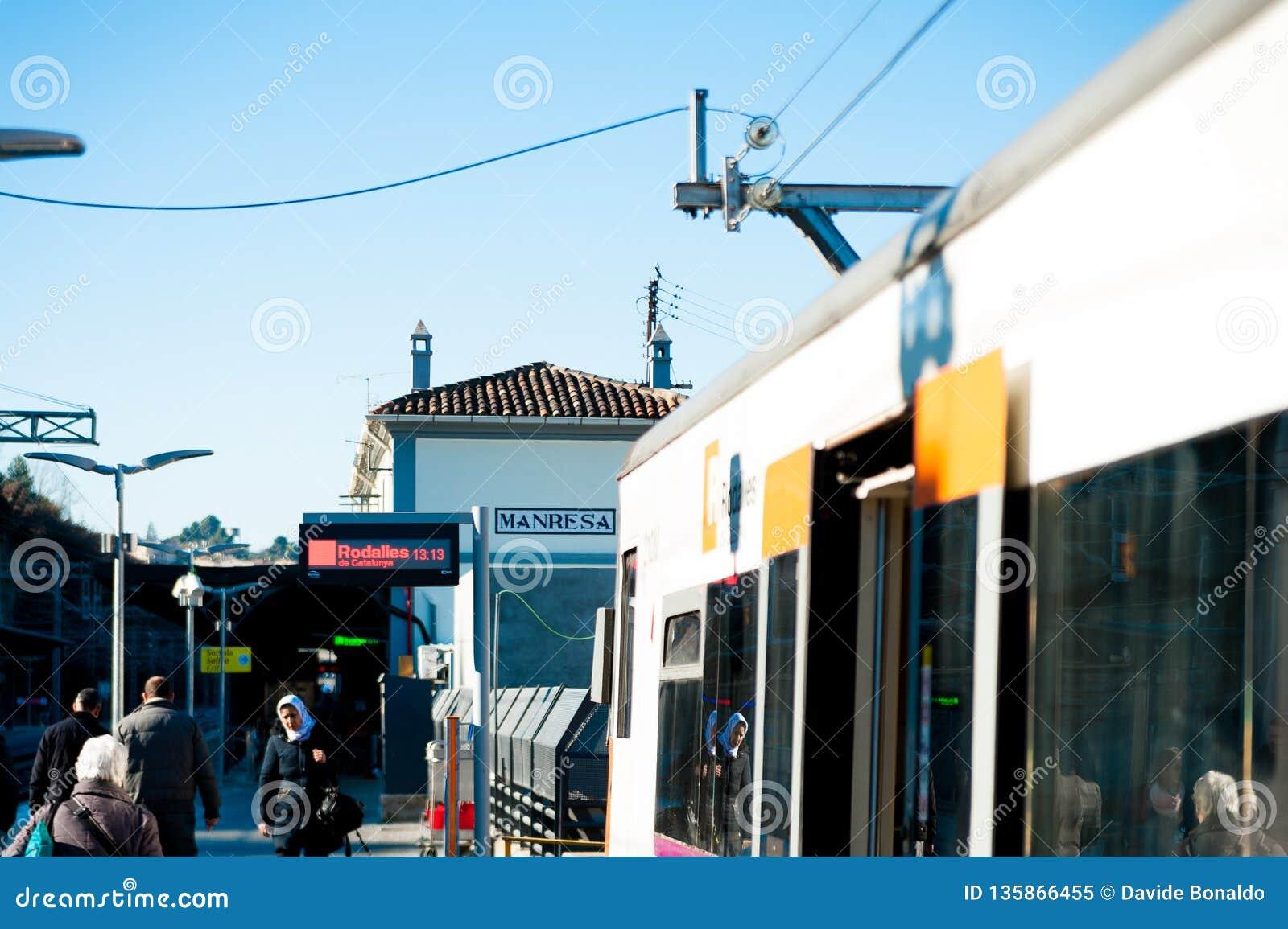 Manresa, Hiszpania - 03 2019 Styczeń: dzielnicowy hiszpański pociąg przyjeżdża w małej stacji kolejowej miasteczko z ludźmi podcz