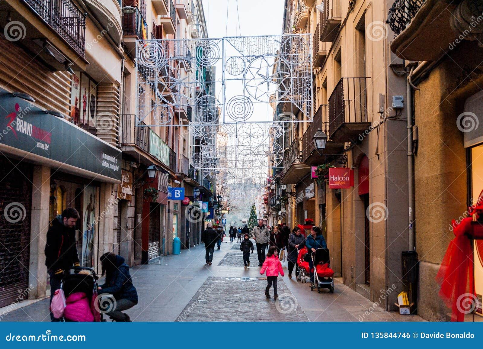 Manresa, Hiszpania - 03 2019 Styczeń: rodziny i dzieci chodzą w ruchliwych ulicach podczas boże narodzenie czasu z światłami i de