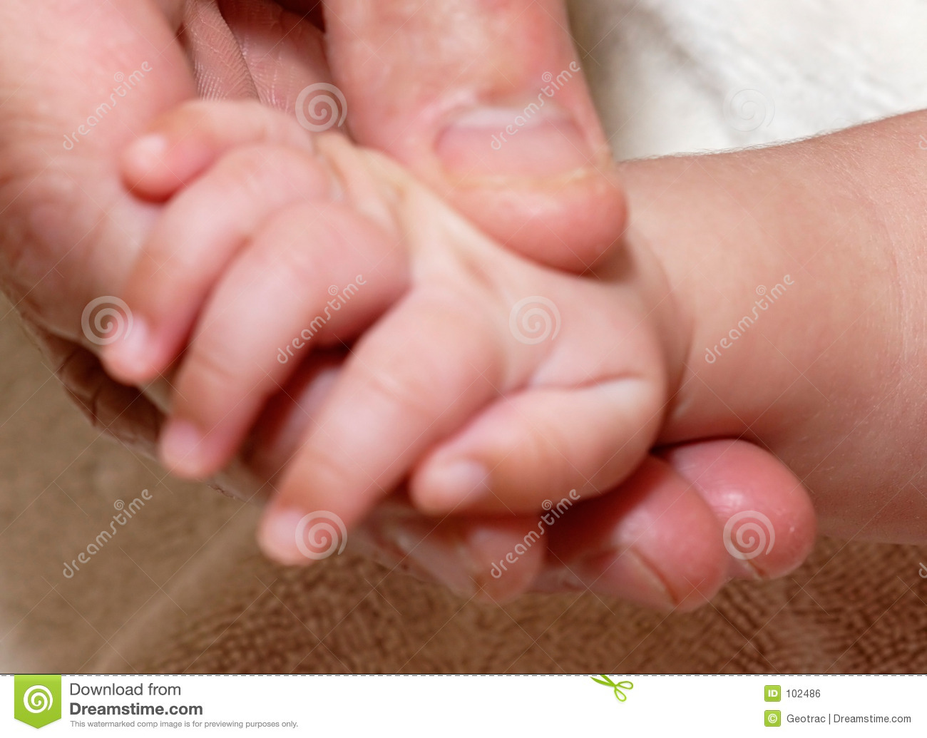Mans hand holding baby hand