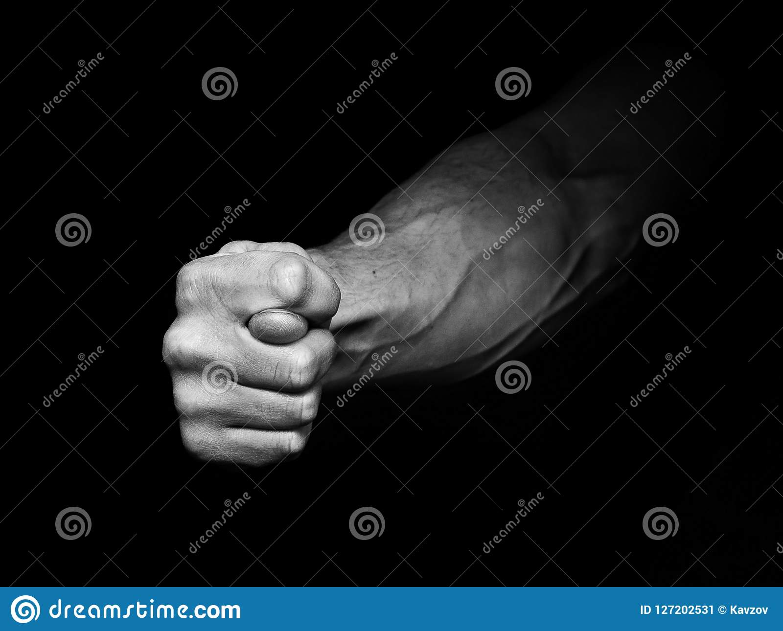 Mans hand showing fig sign in the dark