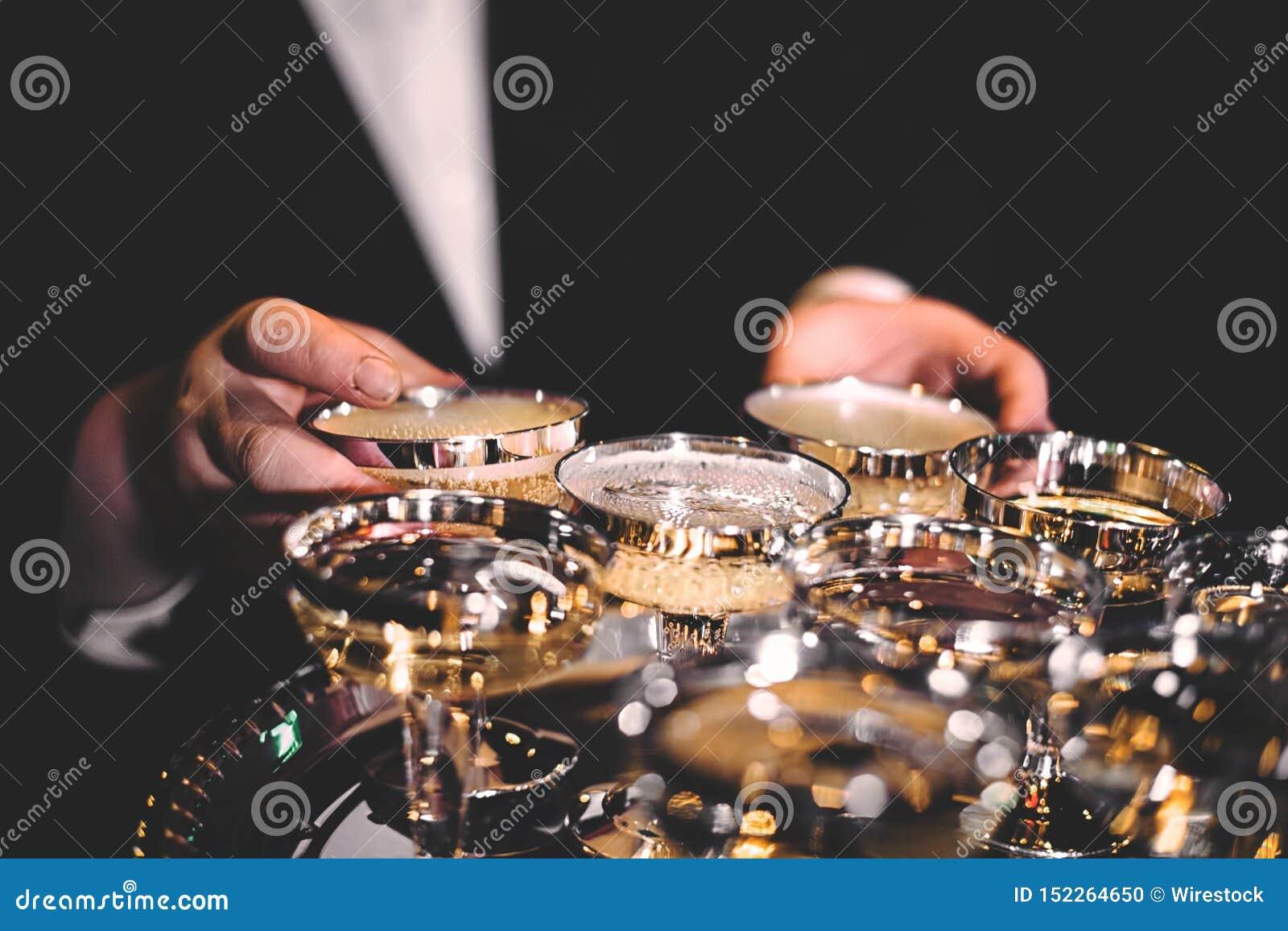 Mans hand som rymmer skinande guld- exponeringsglas av champagne i ett mörkt rum