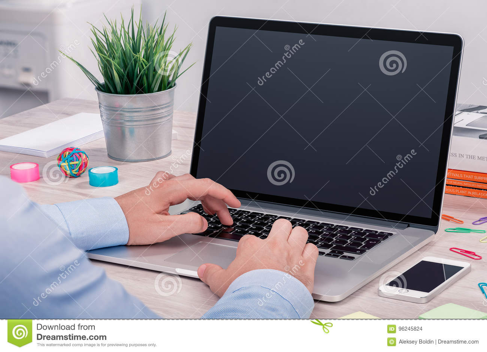Mans hands keyboarding on macbook laptop with blank screen mockup