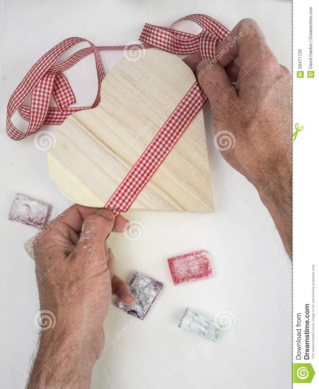 Uncategorized Tying Ribbon mans hands tying ribbon on a heart shaped gift box and with tur royalty free stock photo