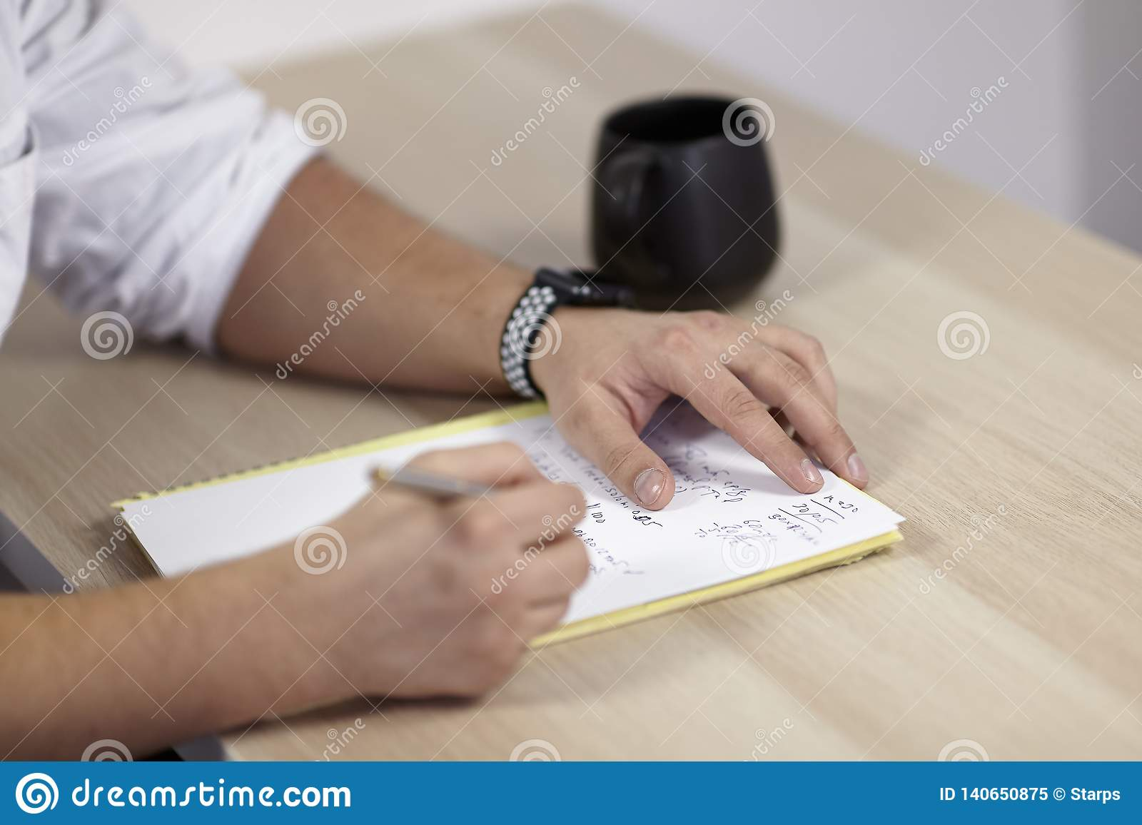 The mans hands on white outfit writes with roller pen on the paper on wooden table some latin, or medicine terms. The cup of tea