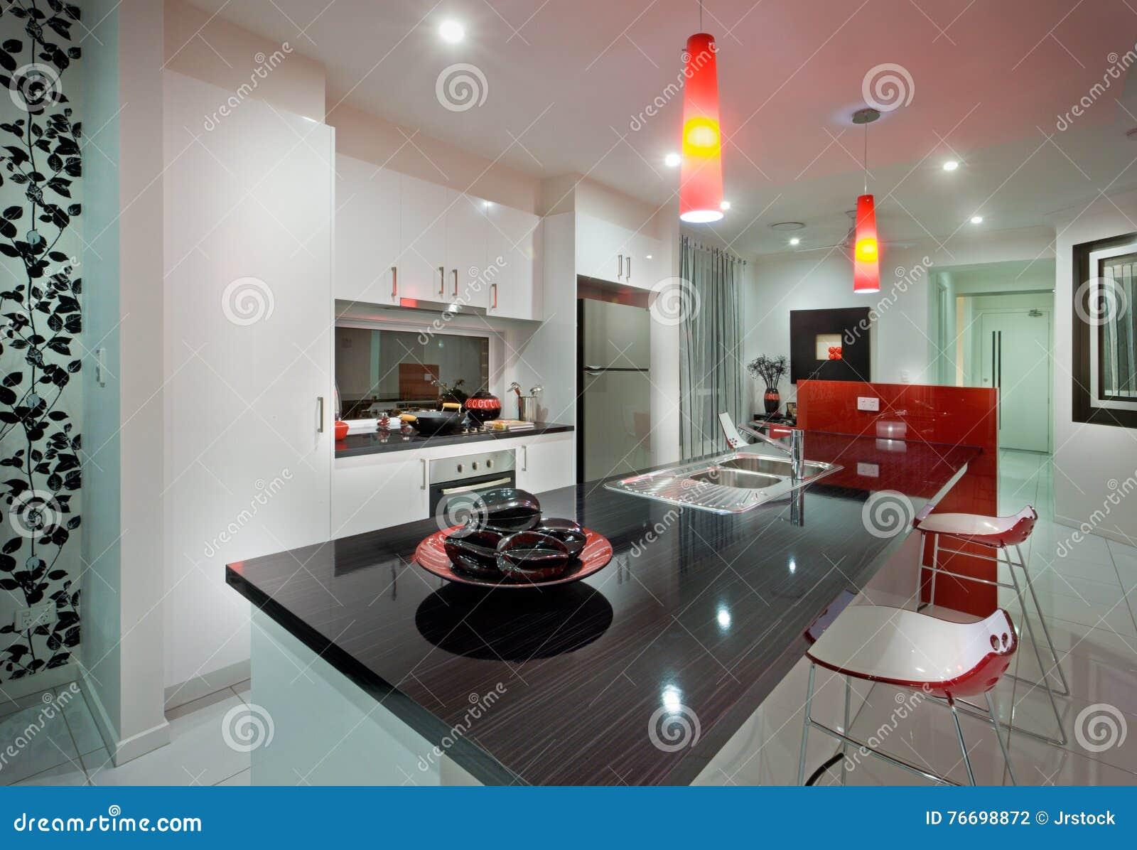 Mansión moderna a través de la cocina con las lámparas rojas