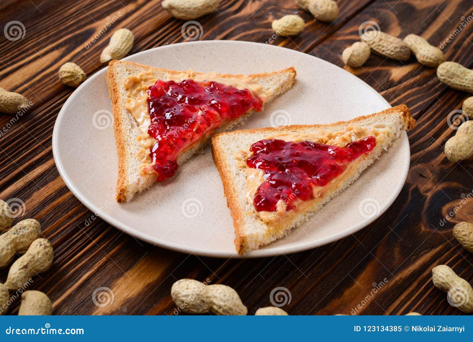 Manteiga de amendoim e sanduíche da geleia no fundo de madeira