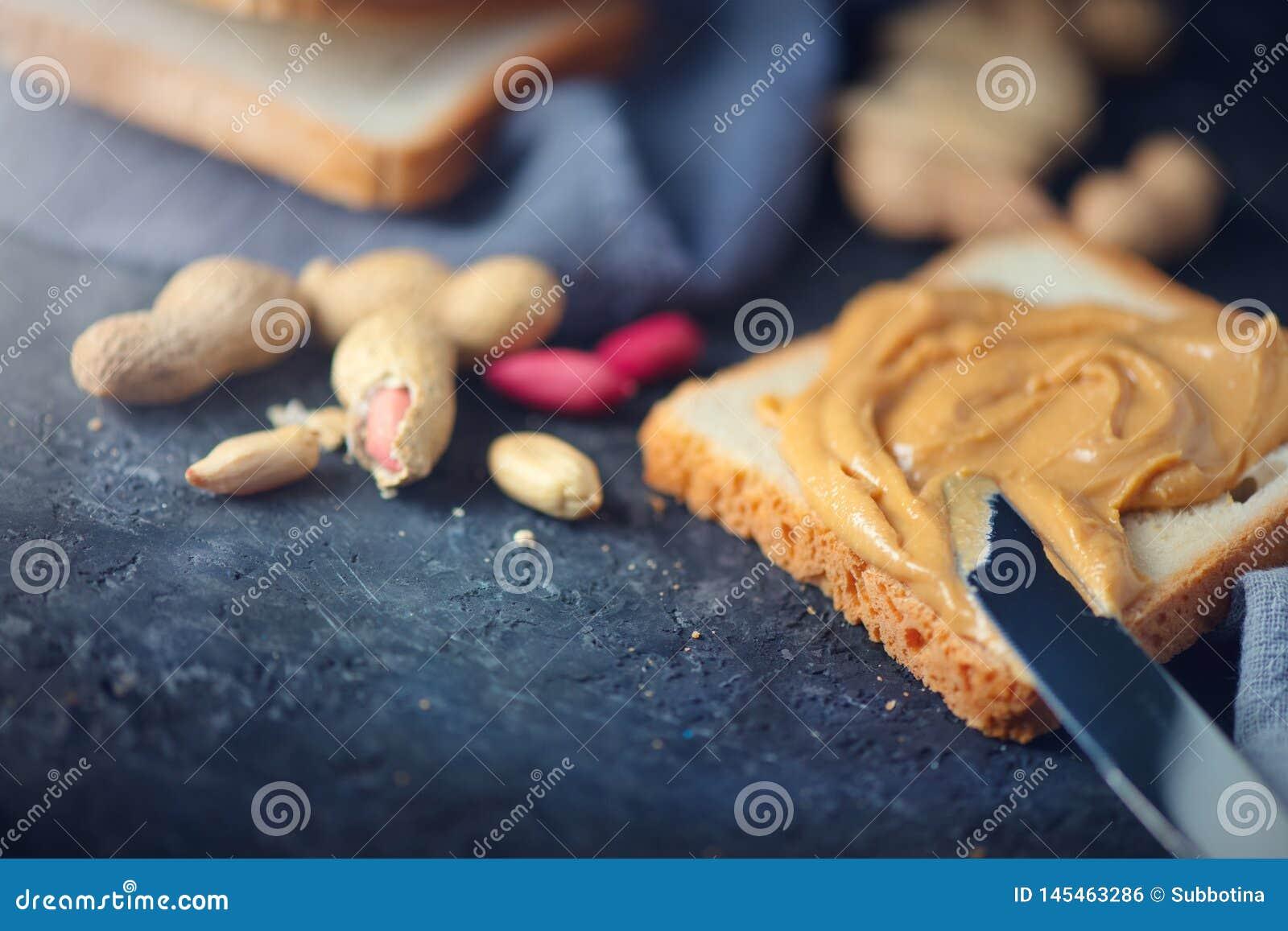 Manteiga de amendoim Pessoa que faz sanduíches da manteiga de amendoim, alimento saudável A mulher mancha a manteiga com uma faca
