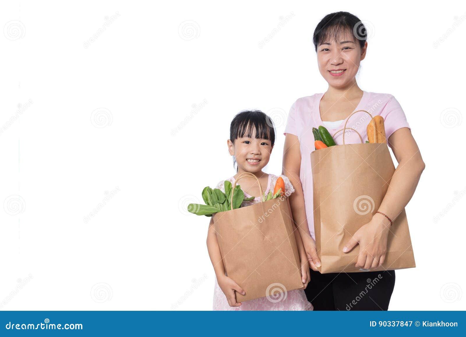Mantimentos levando asiáticos da mulher e da filha